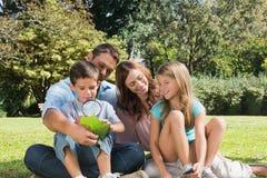 Familia feliz en un parque con el padre y el hijo que examinan la hoja con Fotos de archivo libres de regalías