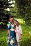 Familia feliz en un paseo en el parque en el aire abierto, la madre y la d Fotos de archivo