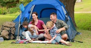 Familia feliz en una acampada delante de su tienda almacen de metraje de vídeo
