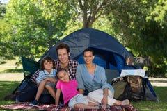 Familia feliz en una acampada en su tienda Foto de archivo