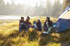 Familia feliz en una acampada que se relaja por su tienda imagen de archivo