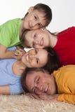 Familia feliz en una alfombra imagenes de archivo