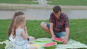 Familia feliz en una comida campestre que come la sandía metrajes