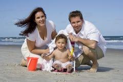 Familia feliz en una playa Imagenes de archivo