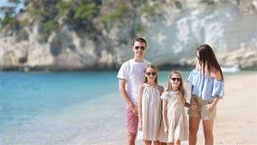 Familia feliz en una playa durante vacaciones de verano almacen de video
