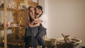 Familia feliz en vacaciones comunes creativas pares románticos que se sientan y que se besan en estudio almacen de metraje de vídeo