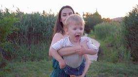 Familia feliz, felices juegos jovenes de la madre con el pequeño hijo lindo que vuela en aire en los brazos de la mamá metrajes
