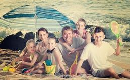 Familia feliz grande en la playa que se sienta el fin de semana Fotos de archivo