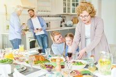 Familia feliz grande que prepara la tabla de cena para el partido fotos de archivo libres de regalías