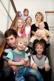 Familia feliz grande que se sienta en las escaleras en casa. Foto de archivo