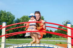 Familia feliz hermosa joven del bebé de la madre y de la hija que juega en el oscilación, y paseo en la sonrisa del parque de atr Foto de archivo libre de regalías