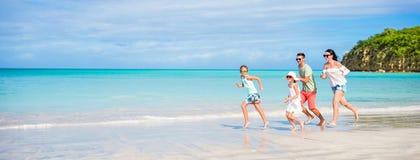 Familia feliz hermosa que corre en la costa Foto de archivo libre de regalías