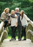Familia feliz hermosa que se une en un puente en el bosque Imagen de archivo