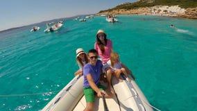 Familia feliz joven con dos niñas en un barco grande durante vacaciones del sammer en Italia