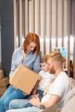 Familia feliz joven con el niño que desempaqueta las cajas junto que se sientan en el sofá imágenes de archivo libres de regalías