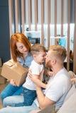 Familia feliz joven con el niño que desempaqueta las cajas junto que se sientan en el sofá foto de archivo