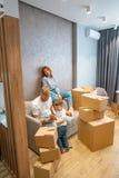 Familia feliz joven con el niño que desempaqueta las cajas junto que se sientan en el sofá fotos de archivo