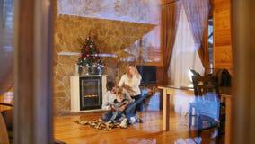 Familia feliz joven con poco bebé que se sienta en el piso en casa acogedora Visión desde la ventana metrajes