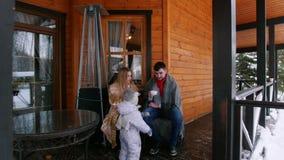 Familia feliz joven con un pequeño bebé que bebe bebidas calientes en el mirador de una casa hermosa almacen de metraje de vídeo
