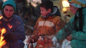 Familia feliz joven del bosque del invierno que se sienta en el bosque por el fuego, bebidas calientes de consumición de los term almacen de video