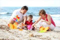 Familia feliz joven en la playa Imagen de archivo libre de regalías