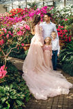 Familia feliz joven en un jardín floreciente de la primavera Fotos de archivo libres de regalías