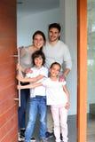 Familia feliz joven que acoge con satisfacción a huéspedes en su hogar Foto de archivo