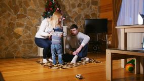 Familia feliz joven que se sienta en el piso en casa acogedora Juegos del niño pequeño con los coches del juguete almacen de video