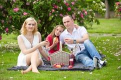 Familia feliz joven que tiene comida campestre al aire libre Imágenes de archivo libres de regalías