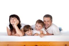 Familia feliz junto en cama Imagen de archivo libre de regalías