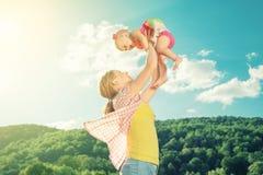 Familia feliz. La madre lanza para arriba al bebé en el cielo Imagenes de archivo