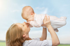 Familia feliz. La madre lanza para arriba al bebé en el cielo Imagen de archivo