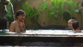 Familia feliz - la madre y el hijo del padre se divierten en su piscina almacen de metraje de vídeo