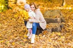 Familia feliz: la pequeña hija de la madre y del niño juega, riendo el abrazo en paseo del otoño en naturaleza al aire libre Fotos de archivo