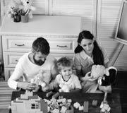 Familia feliz Los padres y el hijo con las caras sonrientes hacen las construcciones de ladrillos imagenes de archivo