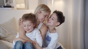 Familia feliz - madre con dos hijos que abrazan en cama almacen de metraje de vídeo