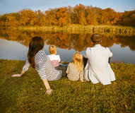 Familia feliz - madre, padre e hijas relajándose en el otoño c Foto de archivo