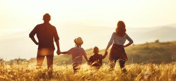 Familia feliz: madre, padre, ni?os hijo e hija en puesta del sol fotografía de archivo
