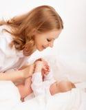 Familia feliz. madre que juega con su bebé en cama Fotos de archivo
