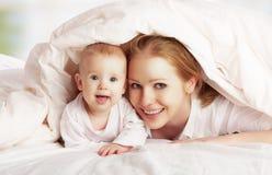 Familia feliz. Madre y bebé que juegan debajo de la manta Foto de archivo libre de regalías