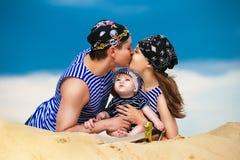 Familia feliz, mamá, papá y pequeño hijo en los chalecos rayados que tienen fu Fotografía de archivo