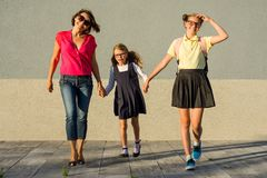 Familia feliz - mamá y colegiala de las hermanas que lleva a cabo las manos imágenes de archivo libres de regalías