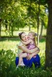 Familia feliz Mentira de la madre y de la hija en una hierba que abrazo adentro imagenes de archivo