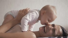 Familia feliz mime a jugar con su bebé en el dormitorio Risa y sonrisa almacen de metraje de vídeo