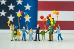 Familia feliz miniatura que sostiene los globos con la nación unida del estado Foto de archivo