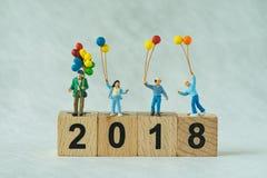 Familia feliz miniatura que sostiene los globos que se colocan en bloque de madera Imagen de archivo libre de regalías