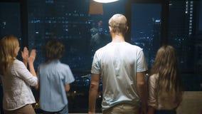 Familia feliz, mujer, hombre y dos niños con una maleta en el fondo de rascacielos en la ventana panorámica adentro almacen de metraje de vídeo