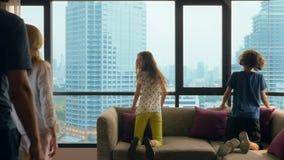 Familia feliz, mujer, hombre y dos niños con una maleta en el fondo de rascacielos en una ventana panorámica almacen de metraje de vídeo