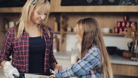 Familia feliz Niña con su mamá que come la leche y las galletas en la cocina, calcio, desayuno, salud A cámara lenta almacen de video