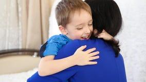 Familia feliz: niño alegre que abraza a su mamá en un sofá blanco en casa metrajes
